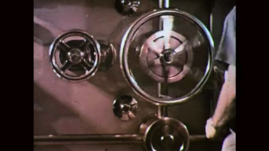 1960s: UNITED STATES: hand turns metal hatch on door