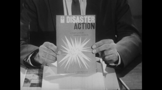 1950s: Expert shows documents for emergency measures. Chief talks and discusses. Chief nods.