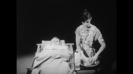 1950s: Assistant nurse prepares wet towel, puts it on forehead of young man. Young patients lay in bed. Assistant nurse measures temperature and looks at watch.