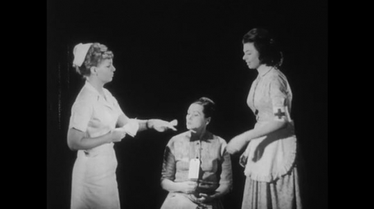 1950s: Nurse helps assistant. Assistant nurse inspects patient's mouth with stick.