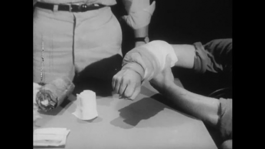 1950s: Patient holds arm with bandage. Nurse talks to man, explains how to give first aid for burns. Man wraps bandage carefully. Nurse observes closely.
