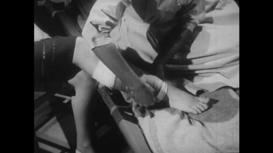 1950s: Nurse bandages leg of patient. Patient vomits into bowl in bed. Man comes and holds head of patient, moves head to the side.