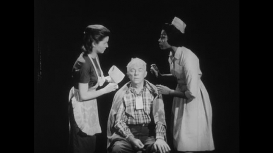 1950s: Nurse explains to assistant how to treat eyes of patient. Nurse leaves. Assistant nurse cleans patient?? eyes.