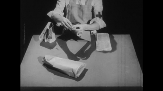 1950s: Assistant nurse folds pair of slippers out of newspapers.