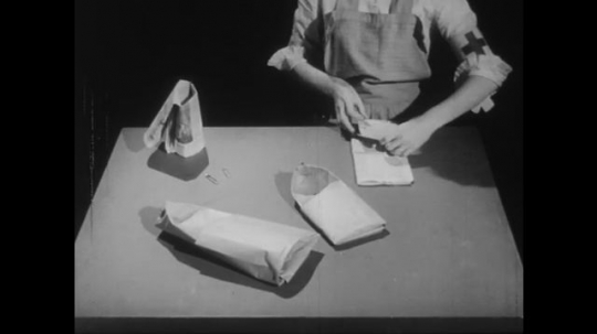 1950s: Assistant nurse folds sole of the slipper out of newspaper, can also be used as bag for disposal purposes.