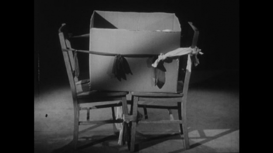 1950s: Cardboard box serves as crib with doll inside. Nurse uses bed sheet to create private zone. Father talks to nurse. Family sits in bed.