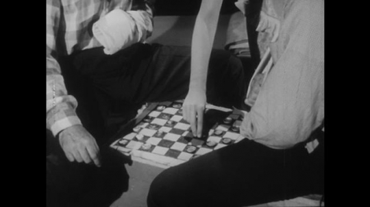 1950s: Nurse stands next to two men. Men sit with checkers board made of cardboard. Nurse moves checkers piece, talks to men. Nurse gives book to injured man. Nurse comforts patient in bed.