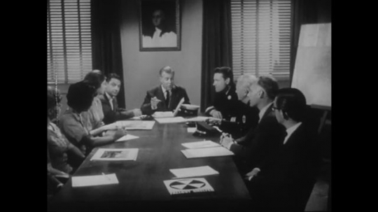 1950s: Director speaks to experts in office. Nurses smile.