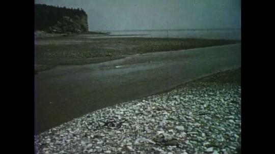 1950s: Low tide reveals rocky beach landscape. Mountain of red sandstone. Stream of water flows down rocks.