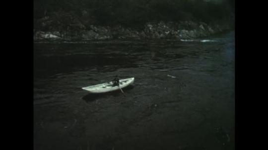 1950s: Man rows boat down river. Man in white boat. Boat circles in river