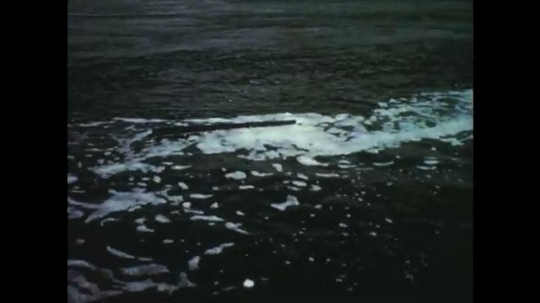 1950s: Foamy water moves. Whirlpool in water. Gentle water current.