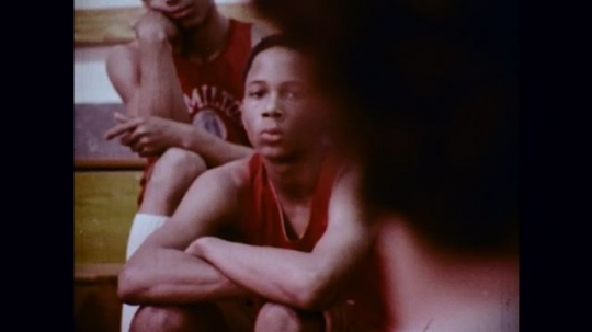 1970s: Basketball players pay attention as their coach instructs them; microscopic view of organisms moving around.