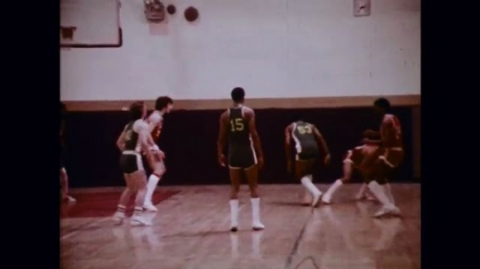 1970s: Basketball team wins a game, crowd rushes the court; scoreboard; closeup of a smile.