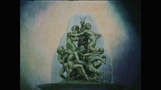 1950s: Animation. Large fountain sprays water. Fountain base is green statue of five nude people frolicking together. Columbus-era explorer ship sails on the sea.