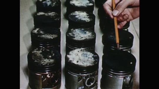 1950s: Man points with pencil at three groups of engine cylinders with varying levels of deposits. Man holds up two spark plugs, one with fewer deposits than the other.