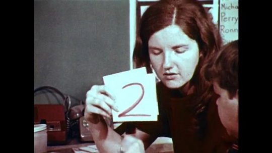 1970s: UNITED STATES: lady holds up numbers on cards. Boy at school. House in street. Man walks along pavement