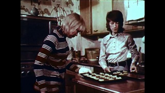 1970s: UNITED STATES: ladies make cakes in kitchen. Girl puts cakes in oven. Boy plays pool.