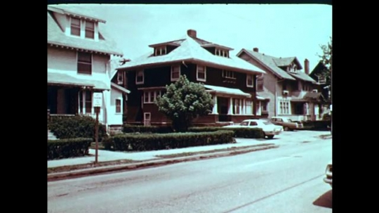 1970s: UNITED STATES: building in street. Door of house. Car drives past house.