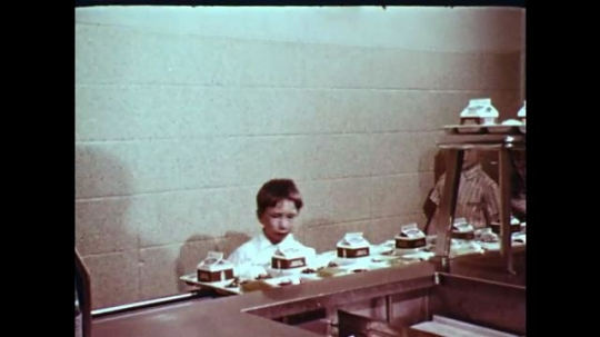 1970s: UNITED STATES: children collect lunch trays from canteen. Girl sits on floor during therapy session