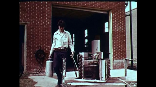 1970s: UNITED STATES: man carries gas cans. Hands draw line on wood. Boy cuts wood with saw
