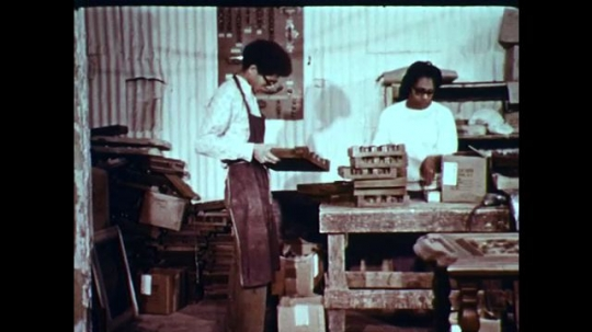 1970s: UNITED STATES: people work in shop. Man sorts post into trays.