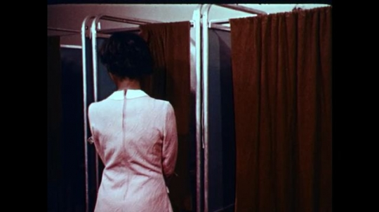 1970s: UNITED STATES: lady in booth. Lady puts paper in file. Ladies cook in kitchen.