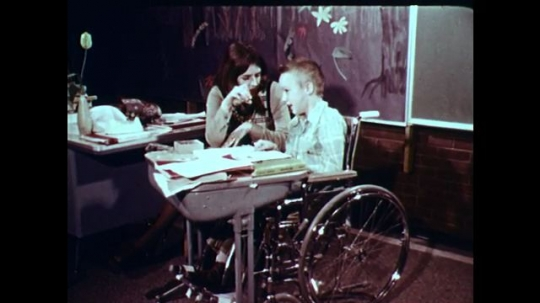 1970s: UNITED STATES: teacher works with boy in wheelchair. Teacher helps children learn with cards