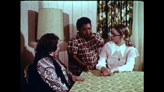 1970s: UNITED STATES: girls talk around table. Boy plays games with friends. Boy makes furniture from wood. Girl at desk. Girl on swing
