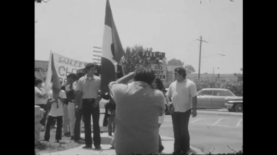 1970s: UNITED STATES: man takes photo of protesters at rally. Speed Limit sign.