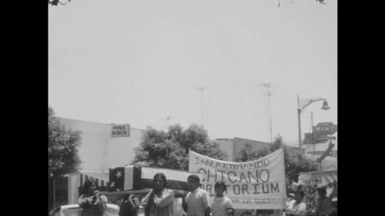 1970s: UNITED STATES: people carry coffin in protest march. Peace symbol on banner