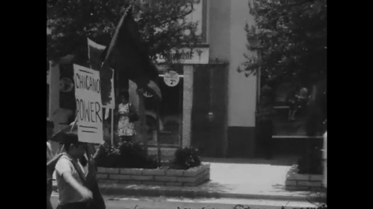 1970s: UNITED STATES: protesters carry flags through street in protests. People clap and chant.