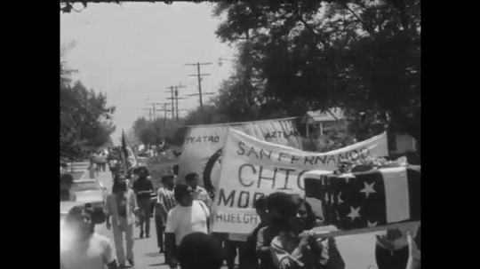 1970s: UNITED STATES: protesters carry flags and banners through streets. People raise fists and chant.
