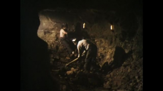 1970s: UNITED STATES: men strike rocks inside mine. Man bangs rocks with hammer. Miner wipes face with handkerchief.