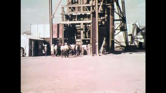 1970s: UNITED STATES: miners at shaft lift. Miners go down on lift. Miners go through tunnel door. Miner tests rocks.