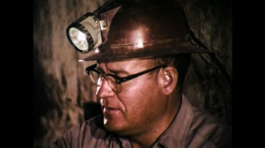 1970s: UNITED STATES: miner tests air in shaft. Ventilation pipe in mine. Man walks under pipe