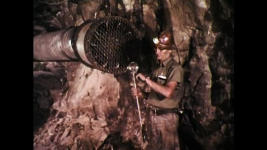 1970s: UNITED STATES: miner tests air flow inside mine shaft with machine.