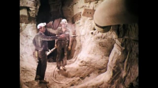 1970s: UNITED STATES: supervisor inspects air flow in mine shaft. Man drills hole in rock by pump.