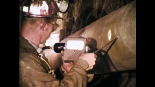 1970s: UNITED STATES: man makes hole in ventilation pipe in mine. Man tests pipe.