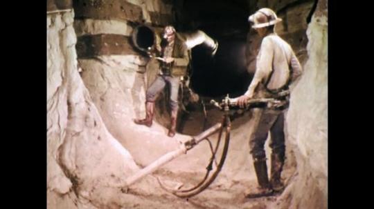 1970s: UNITED STATES: men assess ventilation pipe inside mine shaft. Pulse rate metre reading