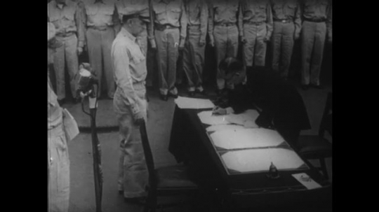 1950s: Japanese Foreign Minister Mamoru Shigemitsu and General Yoshijir? Umezu sign the Instrument of Surrender as Douglas MacArthur, USA navy and photographers stand on deck of USS Missouri.