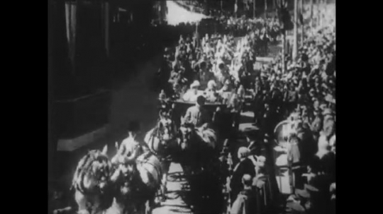 1950s: King George V rides on a royal horse drawn carriage in parade and in a casket as soldiers pull the funeral procession down street.