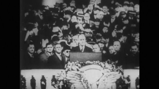 1950s: franklin delano roosevelt speaks at inaugration.flag for NRA. man escorts woman past photographers. charles lindbergh enters courtroom. Bruno Hauptmann sits in crowd.