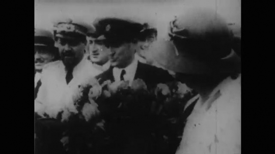 1950s: amelia earhart holds flowers in a crowd and straps on aviator hat. will rogers looks down and talks.