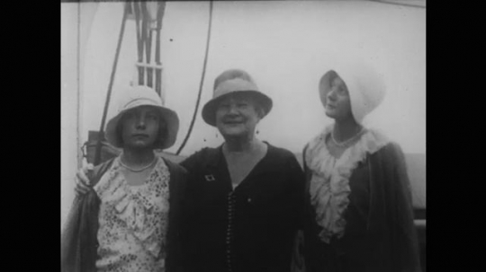 1950s: opera singer Ernestine Schumann-Heink smiles on boat with women. Ruth St. Denis directs women in white gowns to dance outdoors on stage and field.