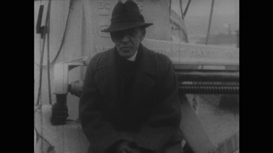 1950s: Russian composer Sergei Vasilievich Rachmaninoff sits, takes off hat and talks on ship. Polish pianist Ignacy Jan Paderewski waves bowler and speaks.