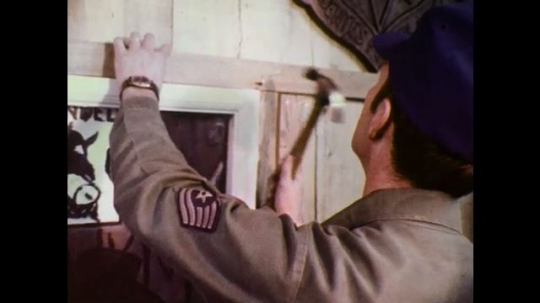 1970s: Man hammers nail. Man hammers doorframe. Wall-mounted rifles next to mirror. Tented straw bed. Welcome sign. Crest and emblems on wall. Man hammers doorframe. Man hammers poster. Wall hanging.