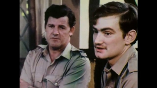 1970s: Two men talking. Man talks and holds block of wood.