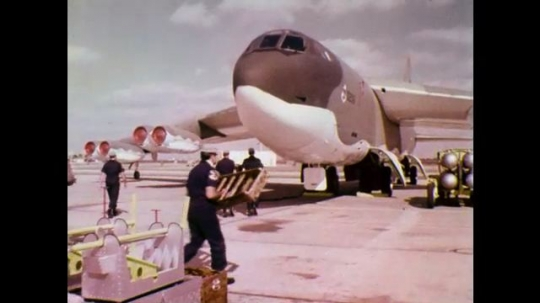 1970s: Men roll gear, weapons, carry ladder toward parked aircraft. Weapons rising up into undercarriage of aircraft.