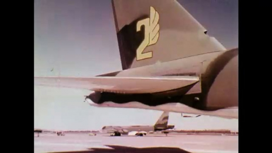 1970s: Wing of airplane. Crests and emblems. Side of airplane. Parked fighter planes. Signage on airplanes. Front of fighter plane.