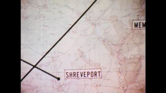 1970s: Map with black route lines. Parked trailers in field. Man in control room. Compass drawing line with pencil.